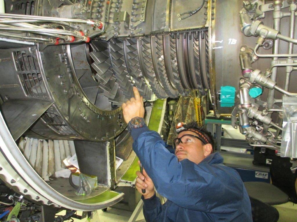 Man running maintenance on airplane engine