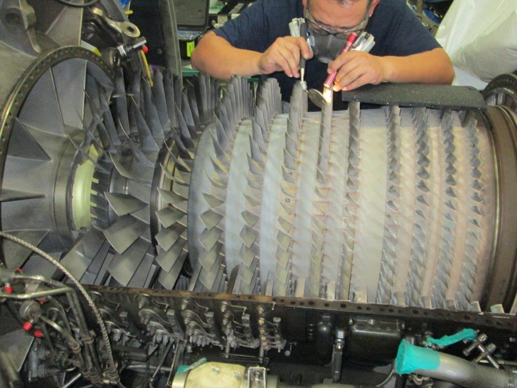 Man repairing airplane engine